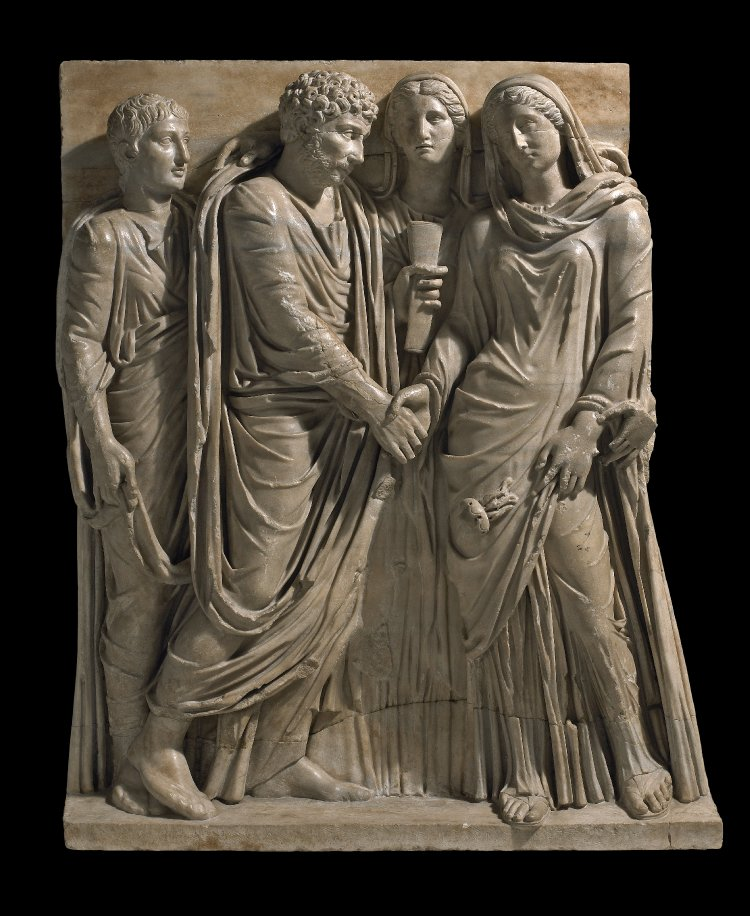 Fragment from the front of a sarcophagus; relief in blue-veined marble with large crystals (probably Proconnesian), showing a Roman marriage ceremony (dextratrum iunctio, literally joining of hands). Between the bride and groom was a figure (now missing) of the god Hymenaeus, who carried the torch used in wedding processions, the flame of which remains against the bride's robes. British Museum #: 1805,0703.143.