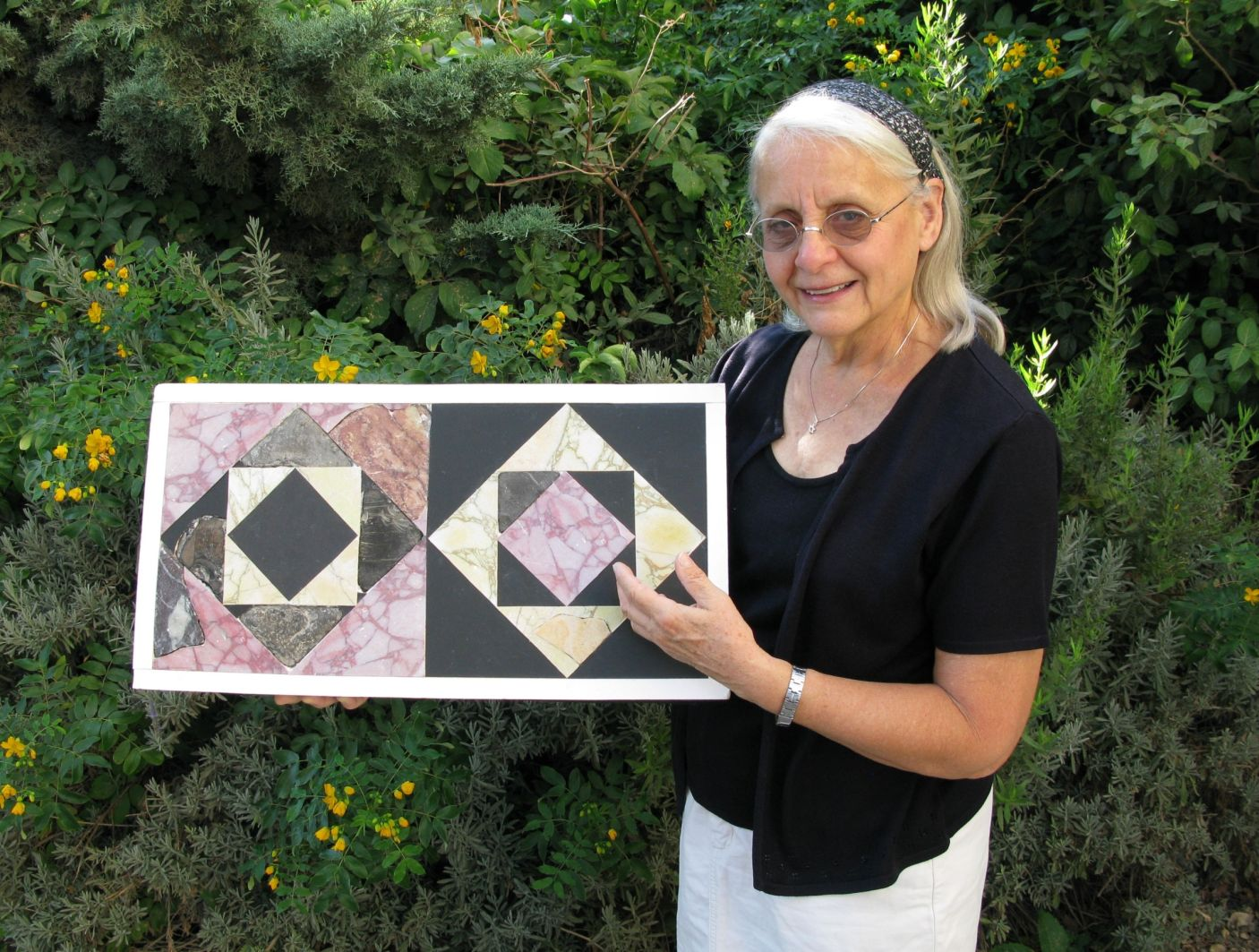 Frankie Snyder showing example of two restored floor tiles from the courtyard of the Second Temple. Photo: Temple Mount Sifting Project