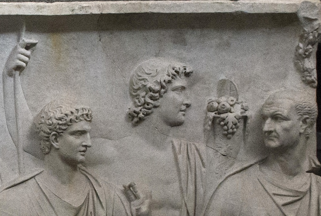 Palazzo Della Cancelleria, Relief B, zoomed in onto Domitian on the left and Vespasian on the right, with most probably Titus in center. Notice Vespasian is balding and has a very simple short haircut, where as Domitian, still a young boy, has the Neronian layered hairstyle.